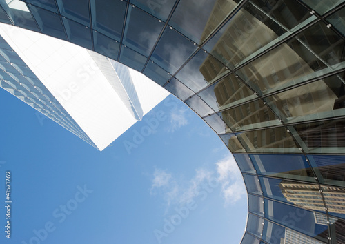 Skyscraper with reflection of buildings on facade, low angle, abstract view
