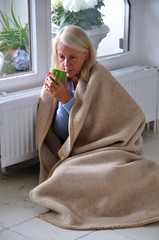 Ältere Frau mit Tee und Decke  friert