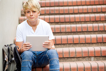 teen boy sitting on stairs and using tablet computer in school