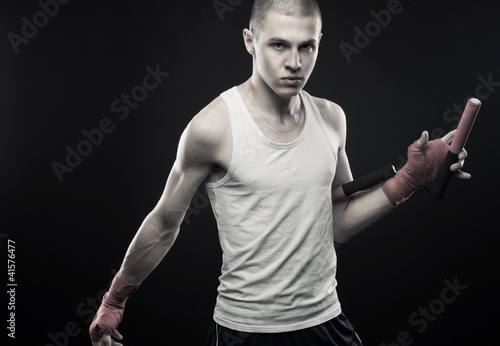 Young man posing with nunchaku