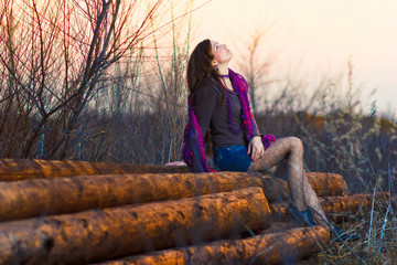 brunette girl sitting woman outside in a group timber planks aut