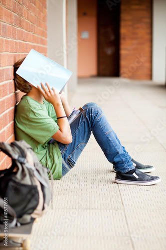 frustrated high school boy using book cover his face
