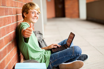 teenage student giving thumb up while using laptop