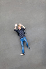 overhead view of a playful teen boy lying on ground
