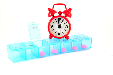 Weekly pill box and red clock on white blackground