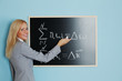 young woman teacher in front of a blackboard