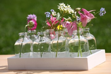 Bunte Gartenblumen in Dekovasen und Holz