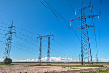 Power line towers on the ploughed field, blue sky and clouds