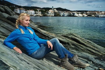 Blond woman against Cadaqués city view.
