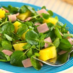 Fresh watercress, pineapple and ham salad on blue plate