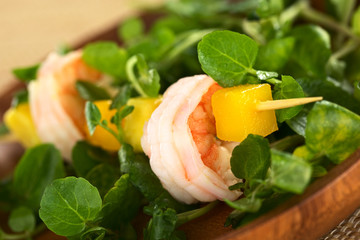 Shrimp, mango and avocado on skewer with watercress