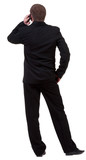 Rear view of business man in black suit  talking on mobile phone