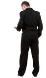 Rear view of business man in black suit  talking on mobile phon