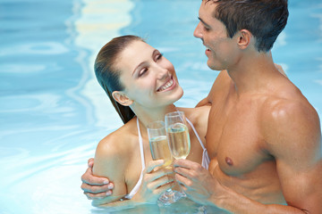 Paar trinkt Sekt im Pool