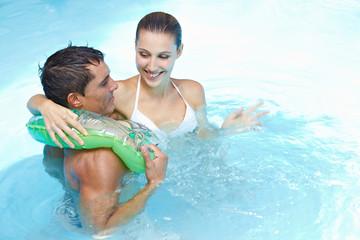 Paar mit Schwimmring im Pool