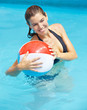 Frau mit Wasserball im Pool