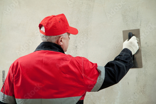 Plasterer in uniform working with float against the wall