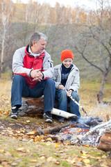 Grandfather and grandson around a campfire