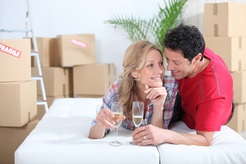 Couple lying on bed celebrating moving into new home