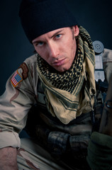 Portrait of soldier against black background.
