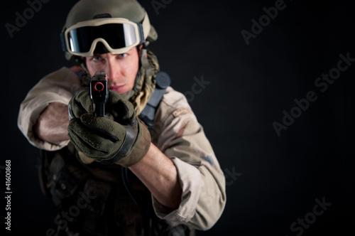 Soldier with gun against black background.