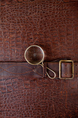 Vintage crocodile leather background with magnifying glass