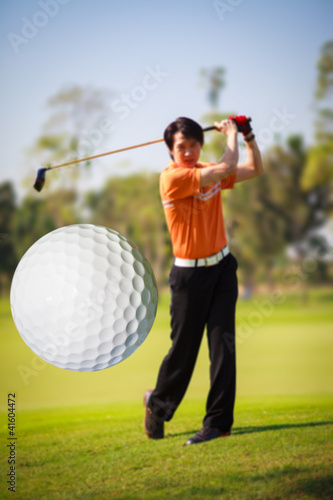 A golf ball just coming off the tee from a golfer in swing