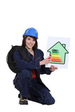 Female electrician holding an energy rating poster