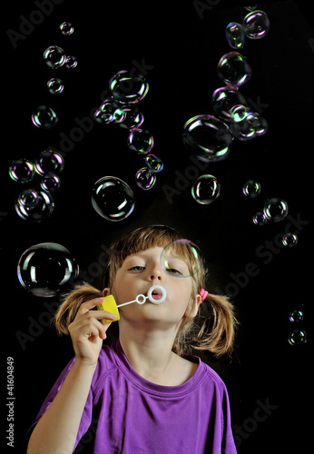 little girl playing - blowing soap bubbles