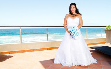 beautiful bride with bouquet and sea view