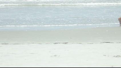 Strand mit Wellen wird von Beinen durchquert