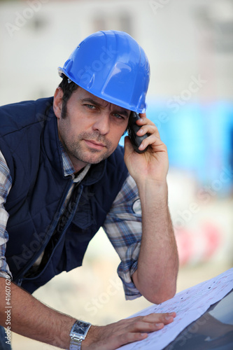 Foreman  checking plans whilst on the phone