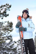 Woman stood on snowy mountain with skis