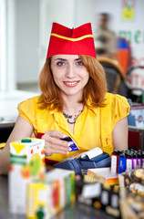 Smiling cashier girl in red and yellow uniform