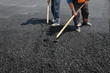 Roadworks, worker with  shovel at asphalt