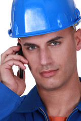 Young worker in boiler suit making call