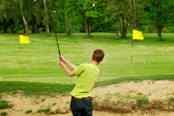 Golfspieler beim Abschlag im Bunker