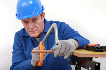 Laborer sawing copper pipe