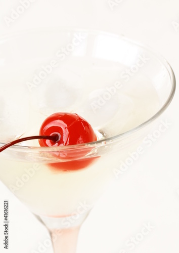 Martini with red cherry in a glass on a white background