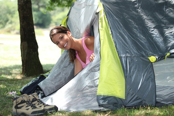 Young woman popping her head out of a tent