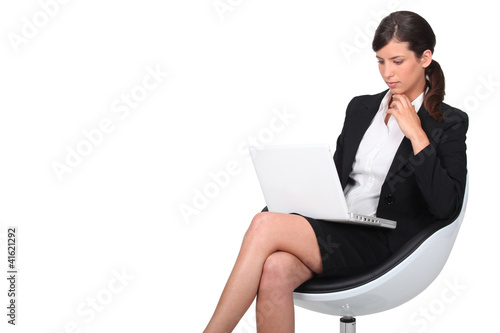 Woman sitting in armchair with computer