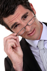Young businessman removing glasses