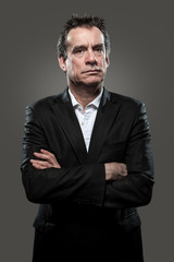 Grumpy Middle Age Business Man in Suit Arms Folded on Grey