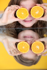 little girl playing with an orange
