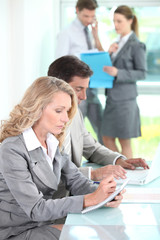 Woman writing in a notepad in an office environment