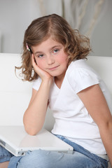 Bored little girl sat with laptop