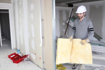 Tradesman installing insulation