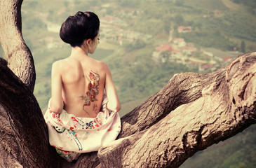 Woman with snake tattoo sitting on tree branch