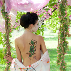Asian style portrait of woman with snake tattoo on her back