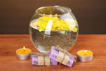Spa composition of bright candles and piece of soap and yellow